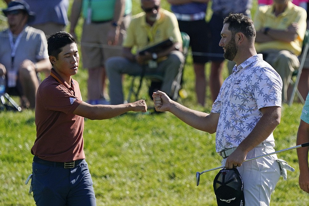 Collin Morikawa fist bumps Jon Rahm following the second round of the Memorial golf tournament, Saturday, June 5, 2021, in Dublin, Ohio. (AP Photo/Darron Cummings)