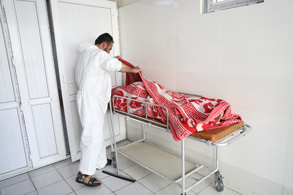 An Afghan health worker checks the body of a woman who died from COVID-19 at the Afghan-Japan Communicable Disease Hospital in Kabul, Afghanistan, Sunday, May 30, 2021. Afghanistan is battling a brutal third wave of COVID infections, while health officials plead for vaccines, expressing deep frustration at the inequities of the global vaccine distribution. Positive COVID cases jump from eight percent to 60 per cent in some parts of the country. (AP Photo/Rahmat Gul)
