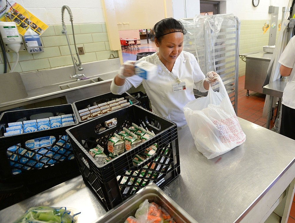 Tang Whittaker, a lunchroom worker at Sutton Elementary School, gathers cartons of milk Thursday, June 3, 2021, while handing out meals to students at the school in Fort Smith. Visit nwaonline.com/210606Daily/ for today's photo gallery. (NWA Democrat-Gazette/Andy Shupe)