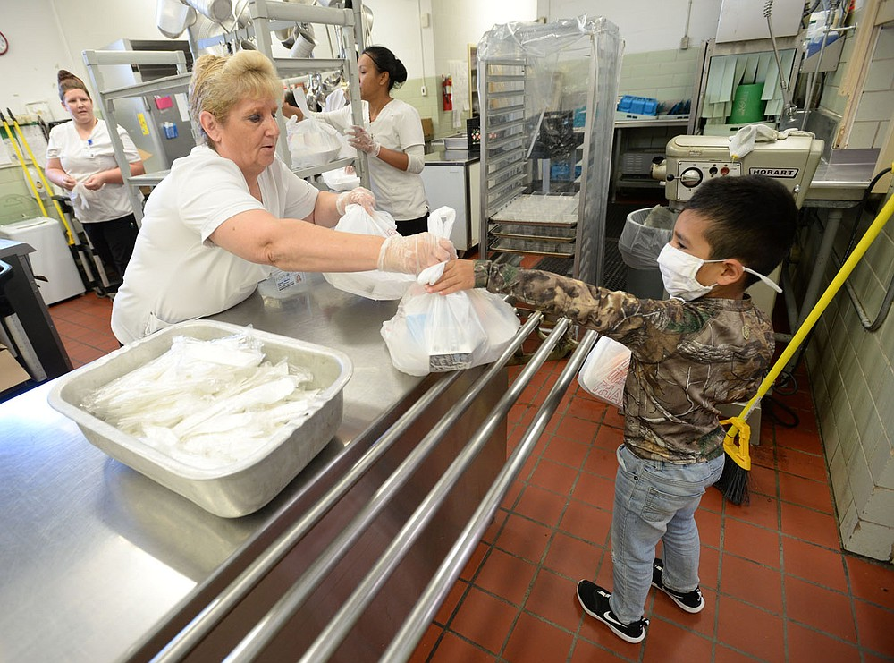 Cindy Wells (left), cafeteria manager at Sutton Elementary School, hands sacked lunches Thursday, June 3, 2021, to Sebastian Uribe, 5, a rising first-grader at the school, while handing out meals to students at the school in Fort Smith. Visit nwaonline.com/210606Daily/ for today's photo gallery. (NWA Democrat-Gazette/Andy Shupe)