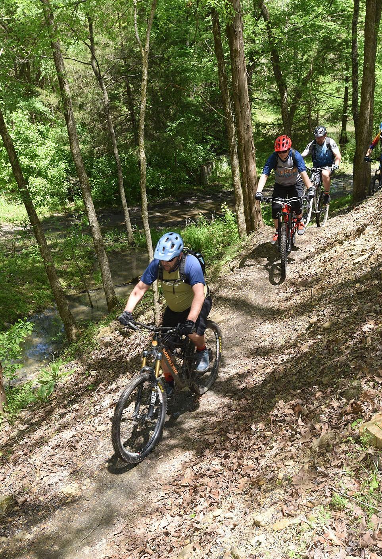 Bikers pedal May 6 2021 along the new Monument Trails system at Devil's Den State Park south of West Fork after dedication ceremonies at the trailhead. (NWA Democrat-Gazette/Flip Putthoff)