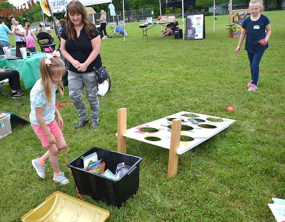 After successfully tossing the bean bag in the holes, one little girl headed for the treasure chest to gather her prize at the Pea Ridge Community Library Summer Reading Kickoff event Saturday, June 5.