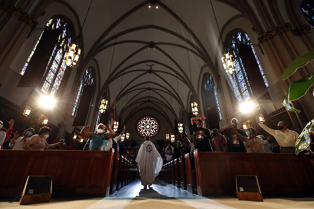 Rev. Michael Pfleger enters to conduct his first Sunday church service as a senior pastor at St. Sabina Catholic Church following his reinstatement by Archdiocese of Chicago after decades-old sexual abuse allegations against minors, Sunday, June 6, 2021, in the Auburn Gresham neighborhood in Chicago. (AP Photo/Shafkat Anowar)