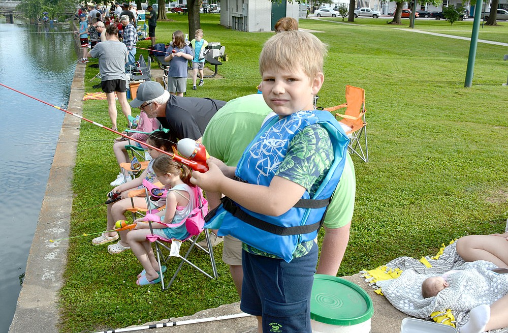 Marc Hayot/Herald-Leader Brandon Melbourne, 8, gets distracted from fishing to pose for a photo at the fishing derby held on Saturday by the Parks and Recreation Department.
