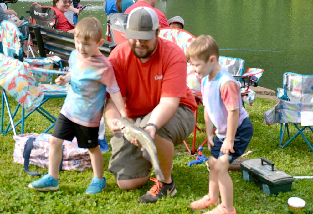Marc Hayot/Herald-Leader Judson Wyatt (right), 4, was one of the big winners of the fishing derby on Saturday. Judson poses with his father Jarred What and his twin brother Jensen Wyatt and their big catch.