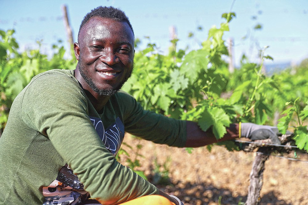 Abo Kouadjo Fulgence, 32 years-old, of Ivory Coast, poses for a picture at the Nardi vineyard in Casal del Bosco, Italy, Friday, May 28, 2021. It is a long way, and a risky one. But for this group of migrants at least it was worth the effort. They come from Ghana, Togo, Sierra Leone, Pakistan, Guinea Bissau, among other countries. They all crossed the Sahara desert, then from Libya the perilous Mediterranean Sea until they reached Italian shores, now they find hope working in the vineyards of Tuscany to make the renown Brunello wine. (AP Photo/Gregorio Borgia)