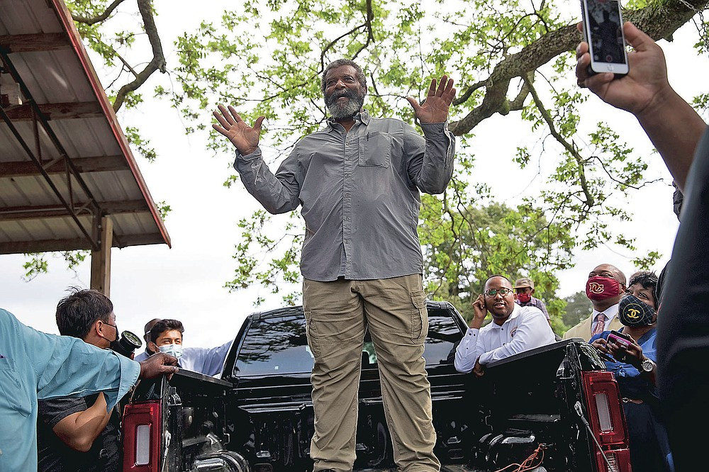 Howard James, owner of Jibbs Vineyard in Byromville, Ga., introduces U.S. Sen. Rev. Raphael Warnock to the crowd of Black farmers gathered at his farm on Tuesday, May 4, 2021.  (Riley Bunch/The Daily Times via AP)