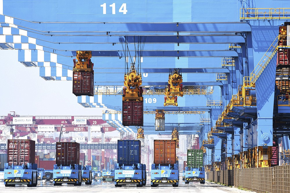 Gantry cranes move containers onto transporters at a port in Qingdao in eastern China's Shandong province Friday, June 4, 2021. China's exports surged nearly 28% in May while imports jumped 51% as demand rebounded in the U.S. and other markets where the pandemic is waning, though growth is leveling off after a stunning recovery from last year's slump. (Chinatopix via AP)