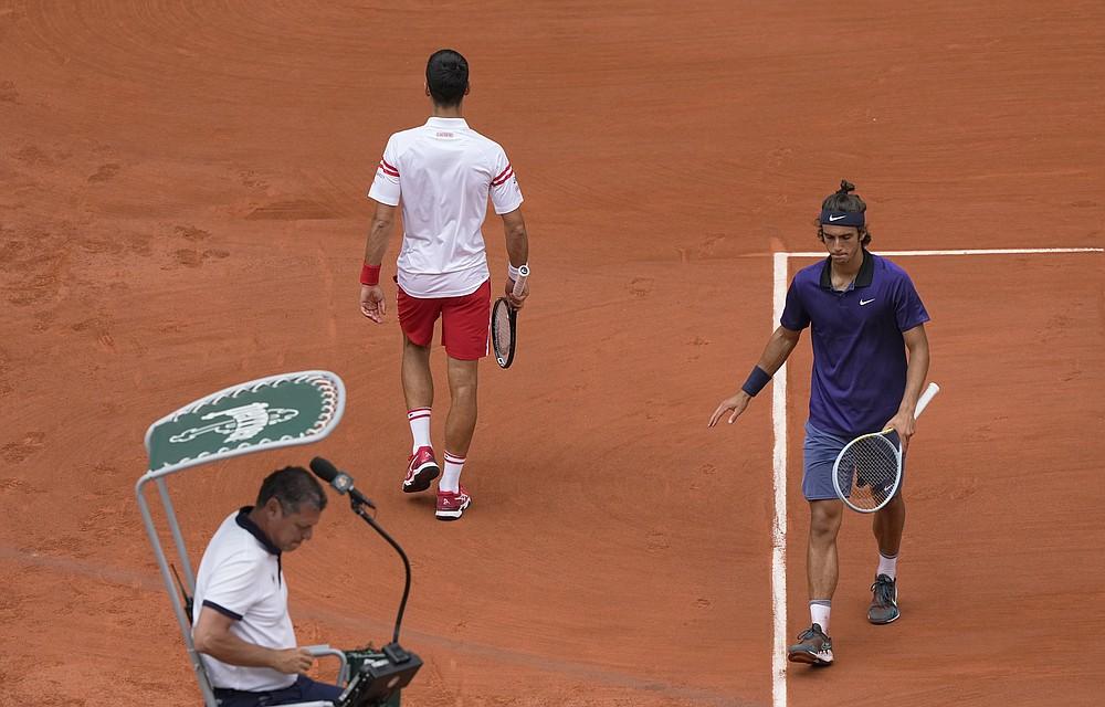 Il serbo Novak Djokovic, in alto a sinistra, passa attraverso l'italiano Lorenzo Mussetti mentre il cambio termina nel tiebreak del secondo set durante la partita del quarto turno del giorno 9 degli Open di Francia al Roland Garros di Parigi, in Francia, lunedì 7 giugno 2021 (AP Photo/ Michel Eulero)