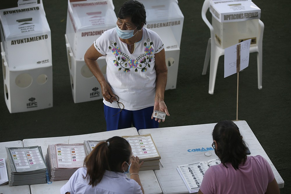A woman shows her ID before voting in Acapulco, Mexico, Sunday, June 6, 2021. Mexicans are electing the entire lower house of Congress, almost half the country's governors and most mayors. (AP Photo/Fernando Llano)
