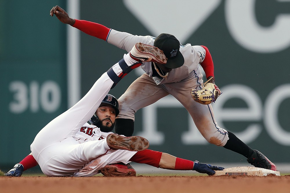 Miami Marlins' Jazz Chisholm Jr., right, tags out Boston Red Sox's Marwin Gonzalez who was trying to advance to second base after hitting a line drive during the fifth inning of a baseball game, Monday, June 7, 2021, in Boston. (AP Photo/Michael Dwyer)