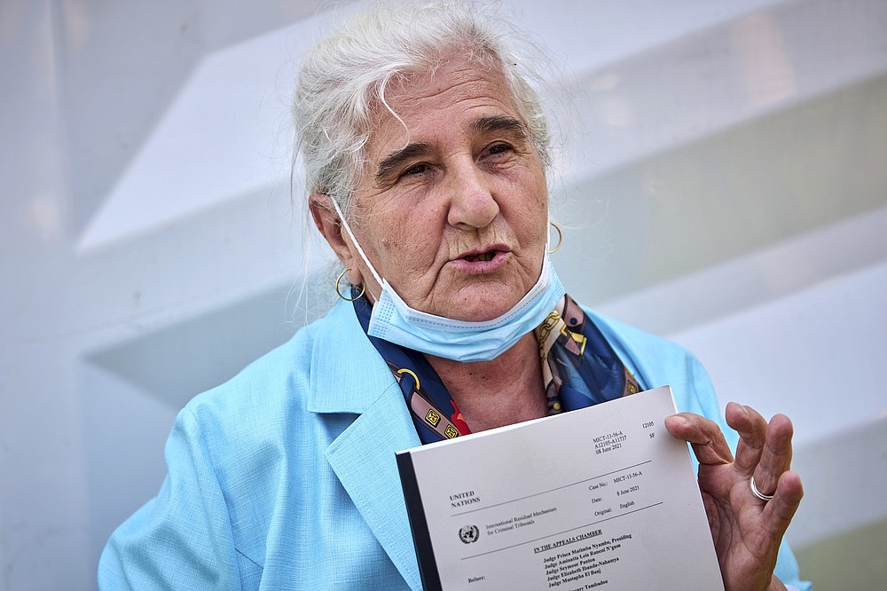 Munira Subasic of the Mothers of Srebenica activist group holds the verdict of the International Residual Mechanism for Criminal Tribunals dismissing Ratko Mladic's appeal, outside the court in The Hague, Netherlands, Tuesday, June 8, 2021. U.N. appeals judges on Tuesday upheld the conviction of former Bosnian Serb military chief Ratko Mladic for genocide and other offenses during Bosnia's 1992-95 war and confirmed his life sentence. (AP Photo/Phil Nijhuis)