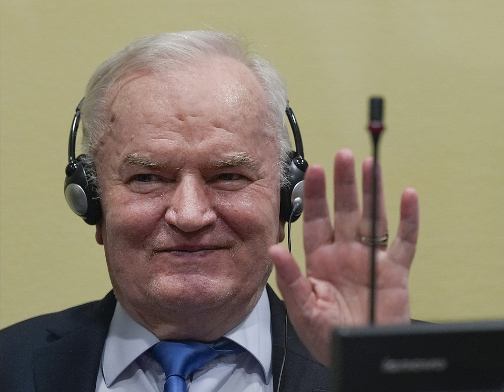 Former Bosnian Serb military chief Ratko Mladic waves in the court room in The Hague, Netherlands, Tuesday, June 8, 2021, where the United Nations court delivers its verdict in the appeal of Mladic against his convictions for genocide and other crimes and his life sentence for masterminding atrocities throughout the Bosnian war. (AP Photo/Peter Dejong, Pool)