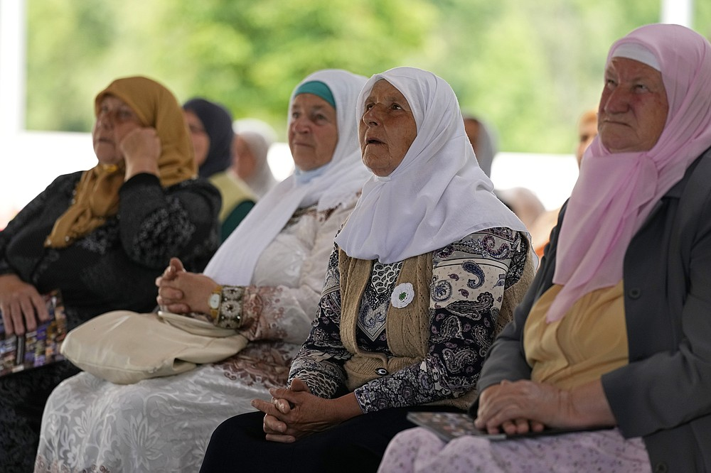 Women from Srebrenica wait to watch a live broadcast from the Yugoslav War Crimes Tribunal in The Hague and learn the verdict for Bosnian Serb military chief Ratko Mladic, at the memorial cemetery in Potocari near Srebrenica, eastern Bosnia, Tuesday, June 8, 2021. The United Nations court delivers its verdict in the appeal by former Bosnian Serb military chief Ratko Mladic against his convictions for genocide and other crimes and his life sentence for masterminding atrocities throughout the Bosnian war.(AP Photo/Darko Bandic)