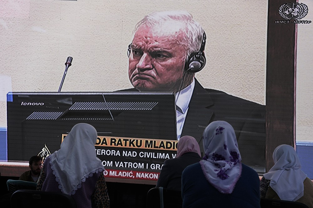 Women from Srebrenica watch a live broadcast from the Yugoslav War Crimes Tribunal in The Hague to learn the verdict for Bosnian Serb military chief Ratko Mladic, on the screen, at the memorial cemetery in Potocari near Srebrenica, eastern Bosnia, Tuesday, June 8, 2021. The United Nations court delivers its verdict in the appeal by former Bosnian Serb military chief Ratko Mladic against his convictions for genocide and other crimes and his life sentence for masterminding atrocities throughout the Bosnian war.(AP Photo/Darko Bandic)