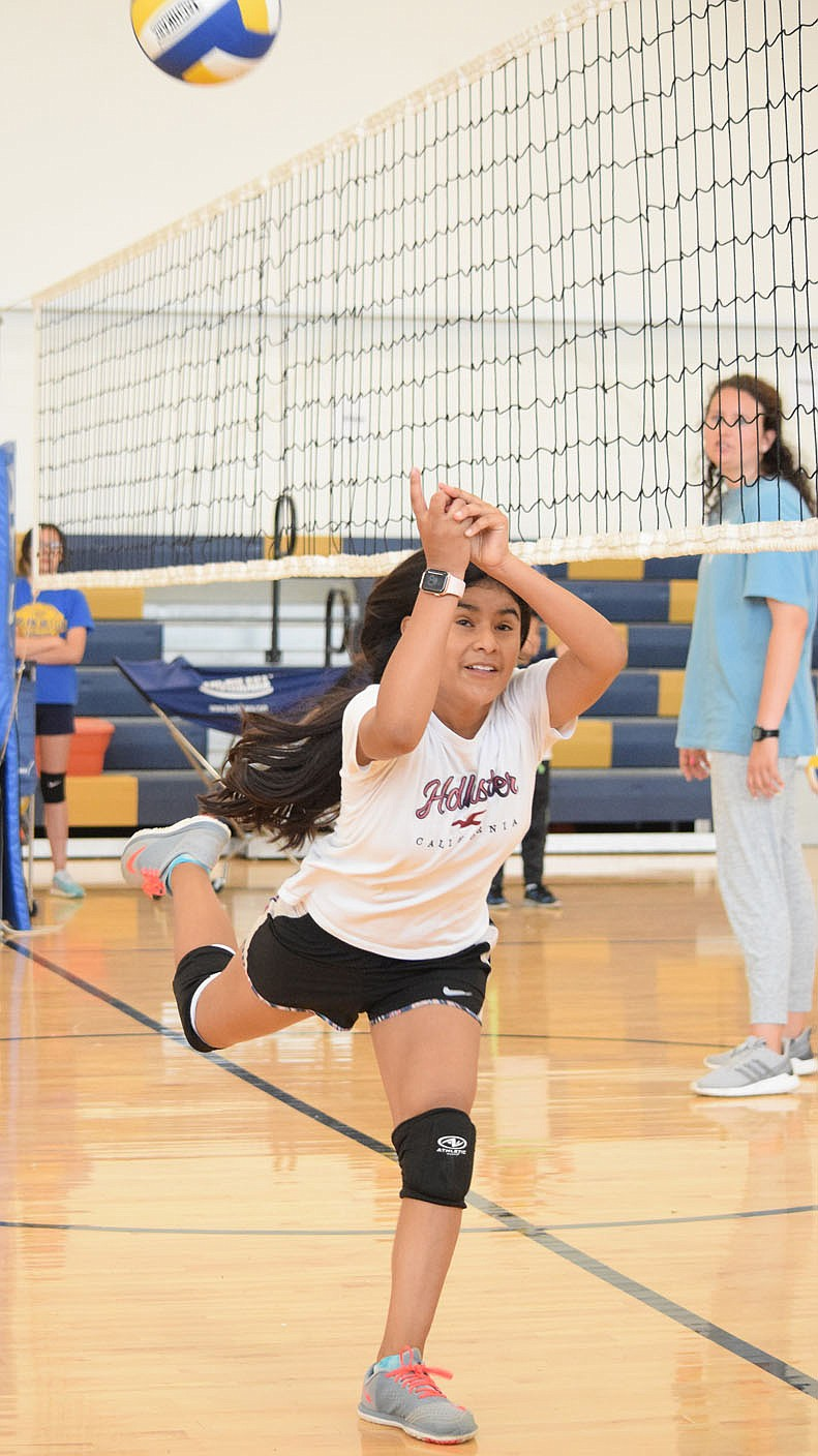 Westside Eagle Observer/MIKE ECKELS Leslie Hernandez manages to catch a ball hit just inside her side of the court during the Lady Bulldog volleyball practice in the gym at Decatur Middle School June 9. Hernandez managed to send the ball to one of her teammates on the other side of the court who sent it back over the net.