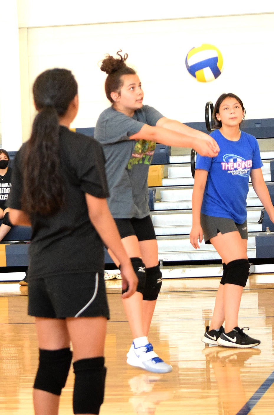 Westside Eagle Observer/MIKE ECKELS Ariana Kumbera (center) uses a forearm hit to move the ball back over the net during the Lady Bulldog junior high volleyball practice session in the gym at Decatur Middle School June 9. Head coach Cali Lankford set up the summer practice sessions to better prepare her players for the upcoming volleyball season.