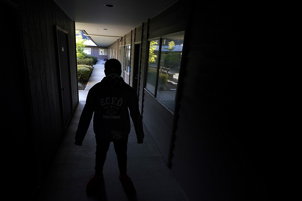 """""""D.Y.,"""" a teenager who is currently living in a foster-care group home, poses for a photo Friday, May 21, 2021, at the facility's administrative office in University Place, Wash. D.Y., who is not being named by the Associated Press to protect his identity, is currently suing the Washington State Department of Children, Youth and Families, alleging that the state has provided inadequate care after bouncing him through more than 50 placements before the COVID-19 pandemic. An Associated Press analysis of state data reveals that the coronavirus pandemic has destabilized the foster care system, leaving children with no parental visits, unprecedented delays in family court cases and limited access to services demanded for reunification. (AP Photo/Ted S. Warren)"""