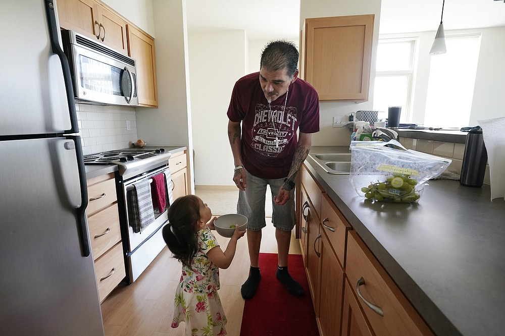 Leroy Pascubillo prepares a snack of grapes for his daughter, who was born addicted to heroin and placed with a foster family at birth, May 10, 2021, in Seattle. Pascubillo, who had used drugs for the better part of four decades, was in a court-ordered in-patient drug rehab program when the pandemic first hit. (AP Photo/Elaine Thompson)