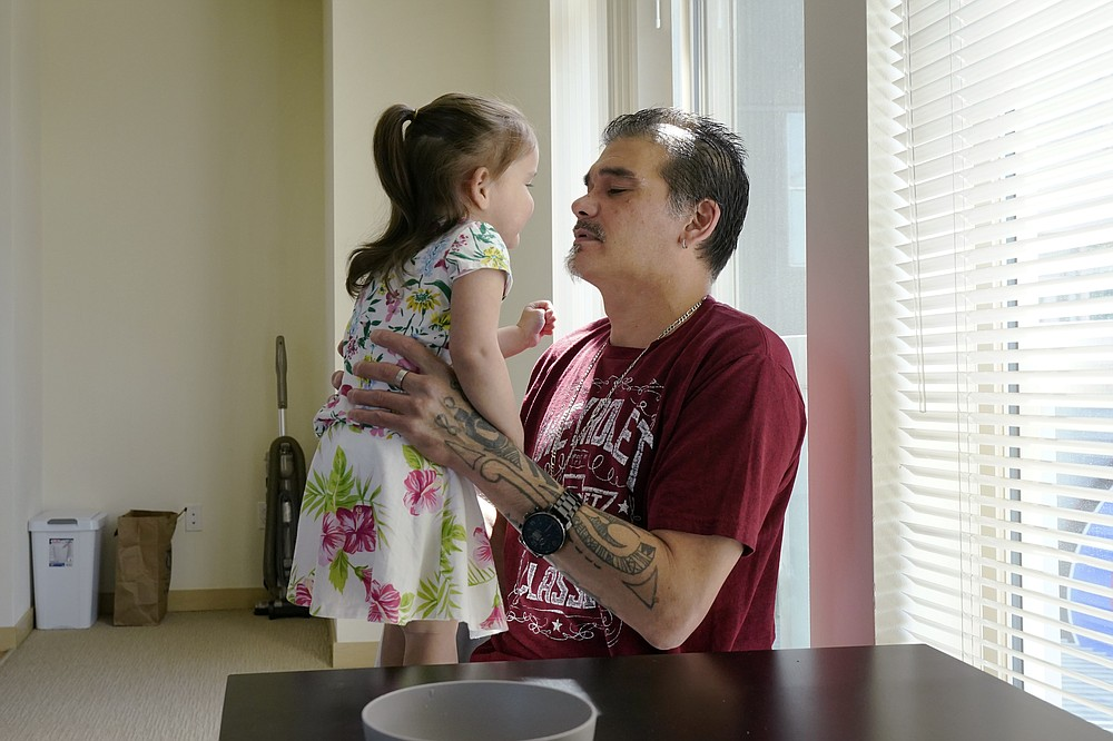 Leroy Pascubillo looks at his daughter, who was born addicted to heroin and placed with a foster family at birth, and talks about his journey regaining custody, May 10, 2021, in Seattle. Pascubillo, who had used drugs for the better part of four decades, was in a court-ordered in-patient drug rehab program when the pandemic first hit. (AP Photo/Elaine Thompson)