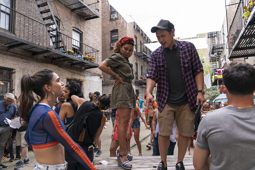 """This image released by Warner Bros. Entertainment shows, Melissa Barrera, from left, Daphne Rubin-Vega and director Jon M. Chu on the set of """"In the Heights,"""" in theaters an HBO Max on June 11. (Macall Polay/Warner Bros. Entertainment via AP)"""