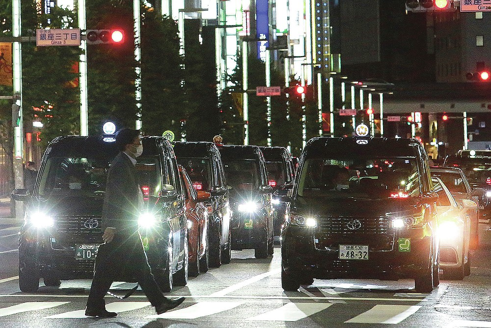 Long lines of taxis wait for customers at street of Ginza shopping district in Tokyo, Tuesday, June 1, 2021, after the 8pm government suggested closing time for restaurants, bars and non-essential businesses under the extended state of emergency. (AP Photo/Koji Sasahara)