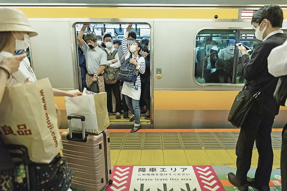 Some passengers try to squeeze themselves into a train after the 8 p.m. government suggested closing time for restaurants, bars and non-essential businesses under the extended state of emergency in Tokyo Monday, May 31, 2021. The 8 p.m. closing time under the emergency has created a new rush hour in Tokyo. (AP Photo/Hiro Komae)