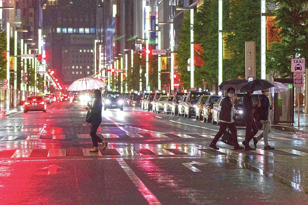 People walk across a traffic intersection as a long line of teaxis wait for customers on a street in the famed Ginza shopping district, where most of the businesses including restaurants, bars and clubs have already closed for the evening under an extended state of emergency in Tokyo on Monday, May 31, 2021. (AP Photo/Hiro Komae)