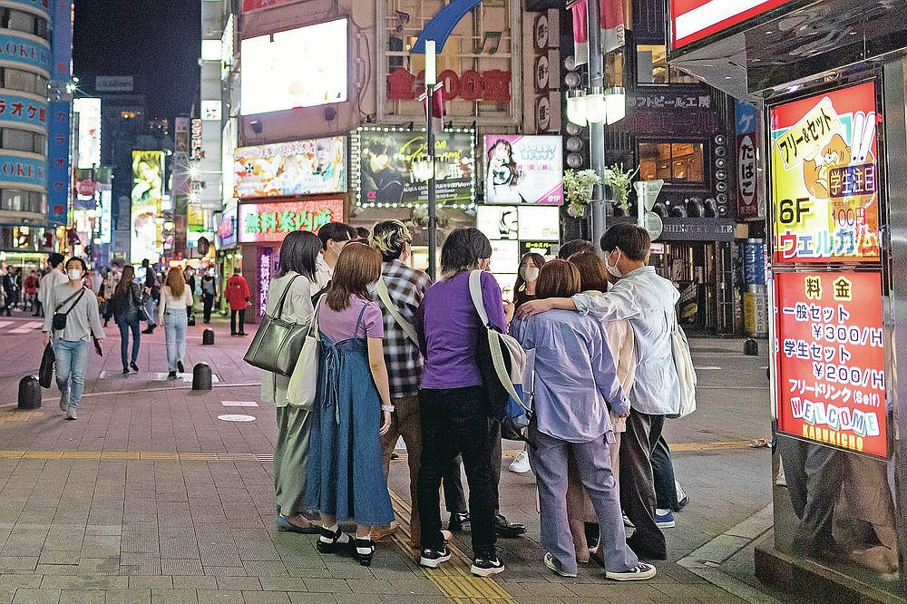 People gather on a street corner in the famed Kabukicho, a night entertainment district in downtown Tokyo, Friday, May 28, 2021, after the 8 p.m. government suggested closing time for restaurants, bars and non-essential businesses under the extended state of emergency. In Tokyo, life in the evening is continuing almost as usual as people in one of the world's least vaccinated countries show increasing signs of frustration and defy largely toothless emergency measures. (AP Photo/Hiro Komae)
