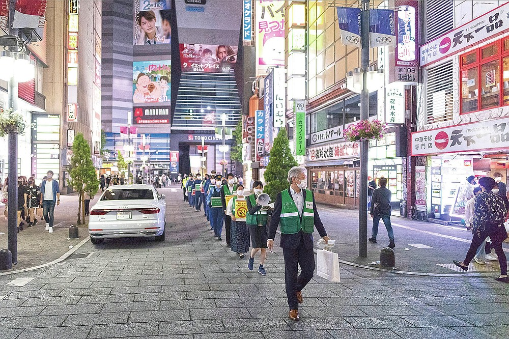 Staff from the Tokyo Metropolitan Government urge people to go home from the Kabukicho entertainment district in the Shinjuku area n Tokyo Friday, May 28, 2021, after the 8 p.m. suggested closing time for restaurants, bars and non-essential businesses under the state of emergency measure. (AP Photo/Hiro Komae)