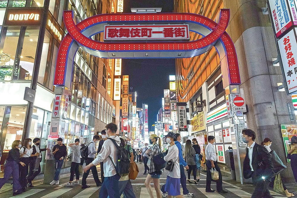 People walk under the main gate to Kabukicho, a night entertainment district in downtown Tokyo, Friday, May 28, 2021, as neon lights on the gate to the area are turned off, but bars along the streets are bustling and brightly lit after the 8 p.m. government suggested closing time for restaurants, bars and non-essential retail businesses under the state of emergency measure. (AP Photo/Hiro Komae)