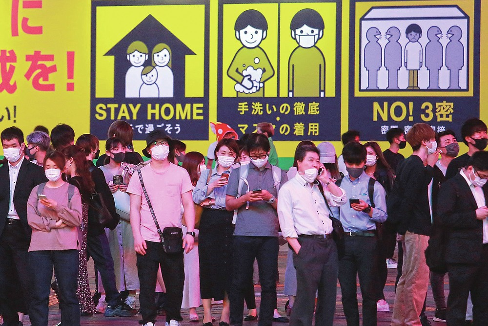 People wearing face masks to protect against the spread of the coronavirus wait at a crosswalk Monday evening, May 31, 2021, in Tokyo. Life in the evening is continuing almost as usual as people in one of the world's least vaccinated countries show increasing signs of frustration and defy largely toothless emergency measures.(AP Photo/Koji Sasahara)