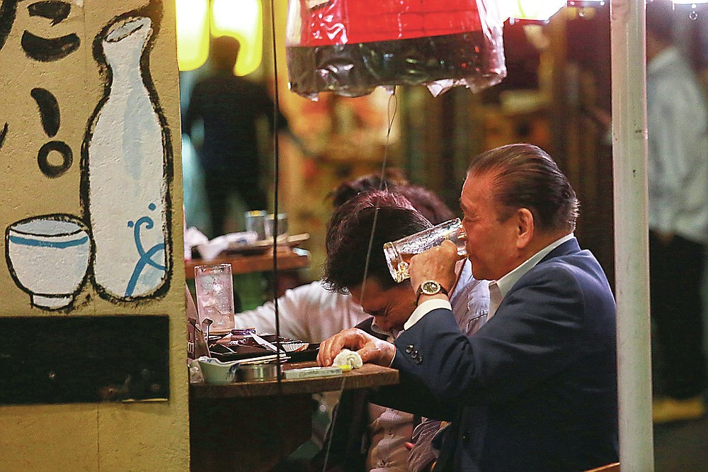 People consume drinks at a bar after the 8 p.m. government suggested closing time under the state of emergency Tuesday, May 25, 2021, in Tokyo. Under the measure, restaurants cannot serve alcohol and must close at 8 p.m. But people can always find bars that are open and packed with customers. (AP Photo/Koji Sasahara)
