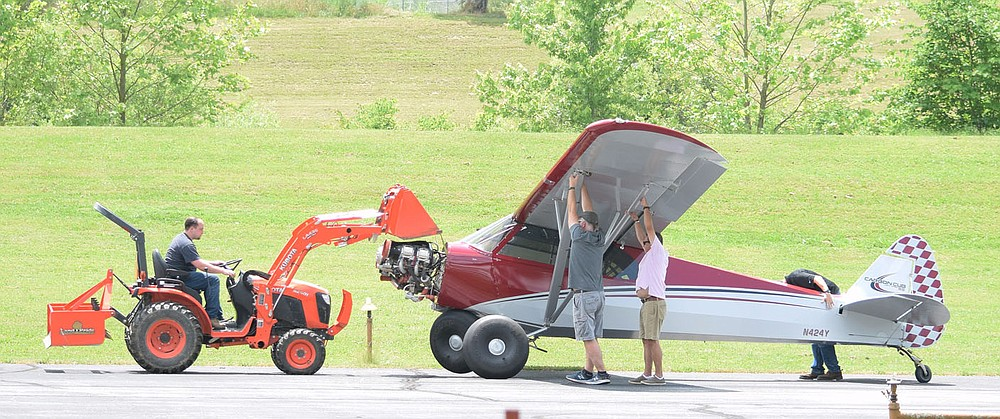 Westside Eagle Observer/MIKE ECKELS  While two men (center) pull down on the left wing, an airport working guides the  Carbon Cub SS to a hanger after a hard land caused the right main landing gear to fold under the front cockpit June 9 at Crystal Lake Airport. Neither crew member was hurt in the incident.