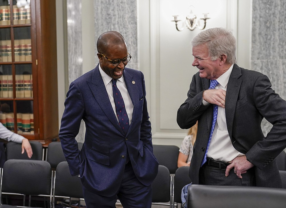 Howard University President Wayne A. I. Frederick, left, speaks with NCAA President Mark Emmert as the Senate Commerce, Science, and Transportation Committee prepares to hold a hearing on student athlete compensation and federal legislative proposals to enable athletes participating in collegiate sports to monetize their name, image, and likeness, at the Capitol in Washington, Wednesday, June 9, 2021. (AP Photo/J. Scott Applewhite)