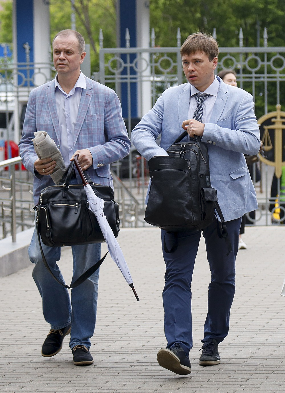 Russian lawyers Ivan Pavlov, left, and Yevgeny Smirnov walk to attend a court session in front of Moscow Court in Moscow, Russia, Wednesday, June 9, 2021. A Moscow court has outlawed the organizations founded by Russian opposition leader Alexei Navalny by labeling them extremist, the latest move in a campaign to silence dissent and bar Kremlin critics from running for parliament in September. The Moscow City Court's ruling, effective immediately, prevents people associated with Navalny's Foundation for Fighting Corruption and his sprawling regional network from seeking public office. (AP Photo/Alexander Zemlianichenko)