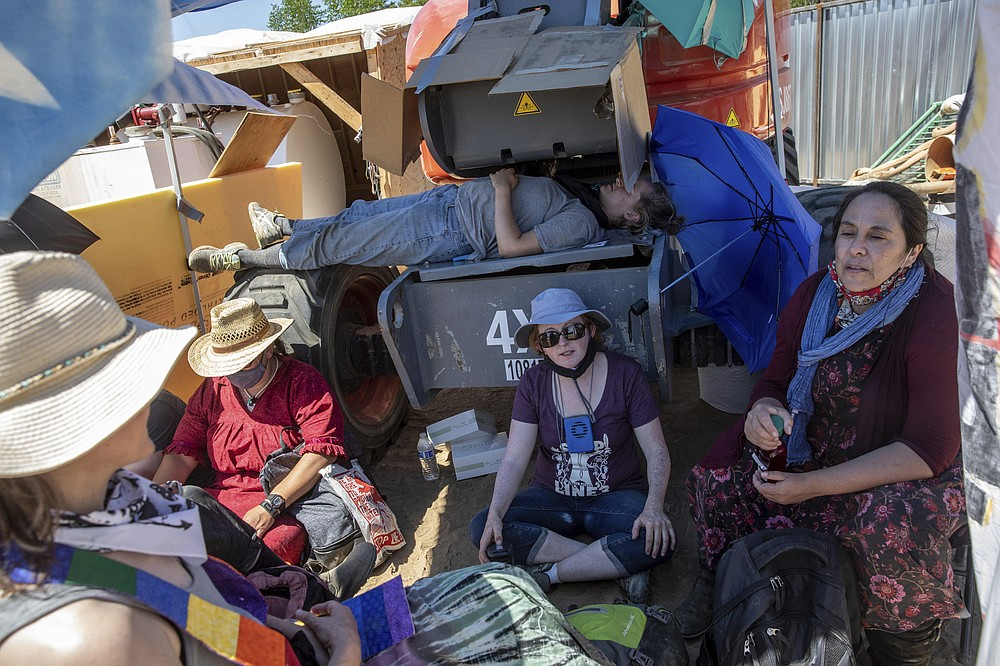 A group of activists sit under a shade as two others sit locked to a piece of construction equipment at an Enbridge Line 3 pump station near Park Rapids, Minn., on Monday, June 7, 2021. (Evan Frost/Minnesota Public Radio via AP)