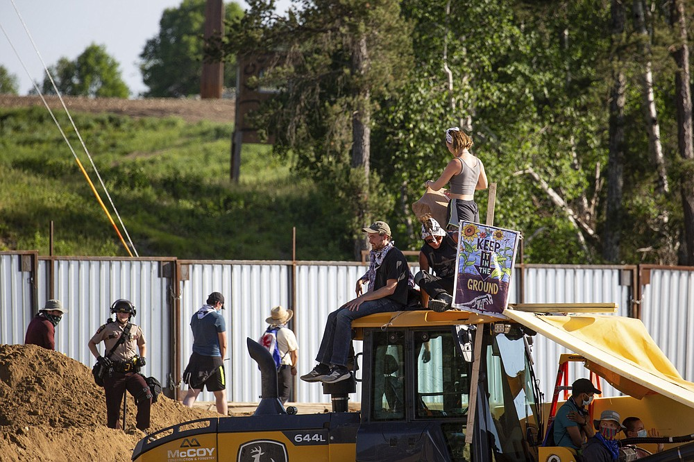 Activists sit on construction equipment while others are arrested and escorted out of an Enbridge Line 3 pump station near Park Rapids, Minn., on Monday, June 7, 2021. (Evan Frost/Minnesota Public Radio via AP)