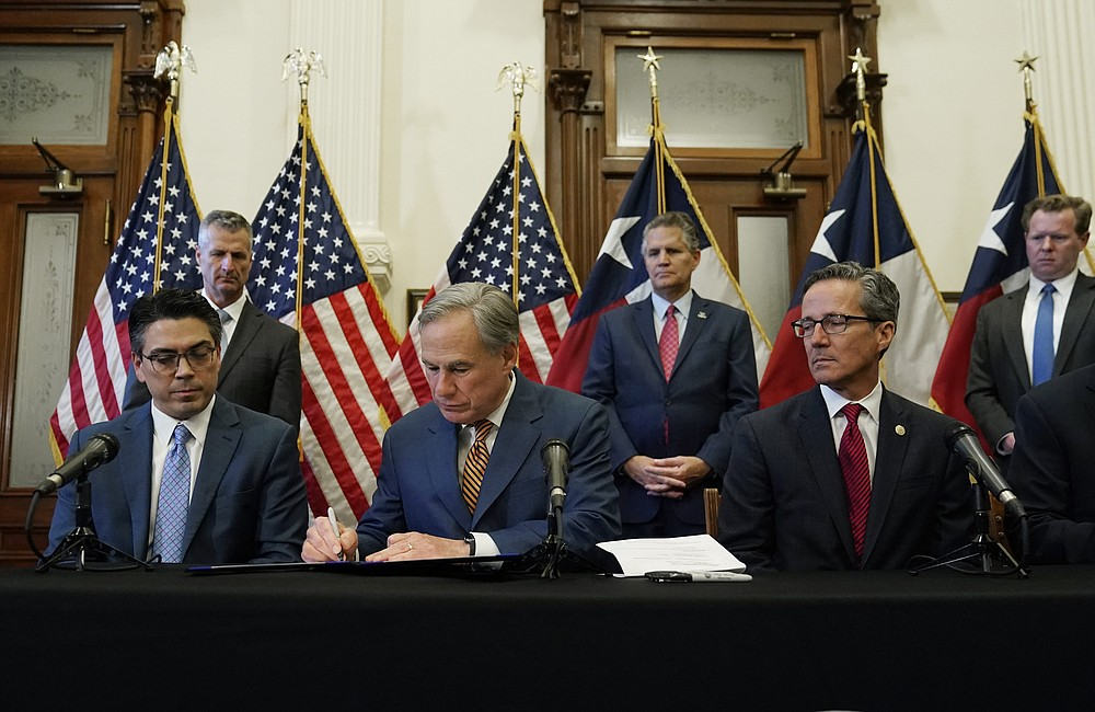 With State Representative Chris Paddie, left, and State Senator Kelly Hancock, right, watching, Texas Gov. Greg Abbott, center, signs two energy-related bills on Tuesday 8 June 2021, in Austin, Texas.  Abbot enacted legislation to reform the Electric Reliability Council of Texas (ERCOT) and alter and improve the reliability of the state's electricity grid.  (AP Photo / Eric Gay)