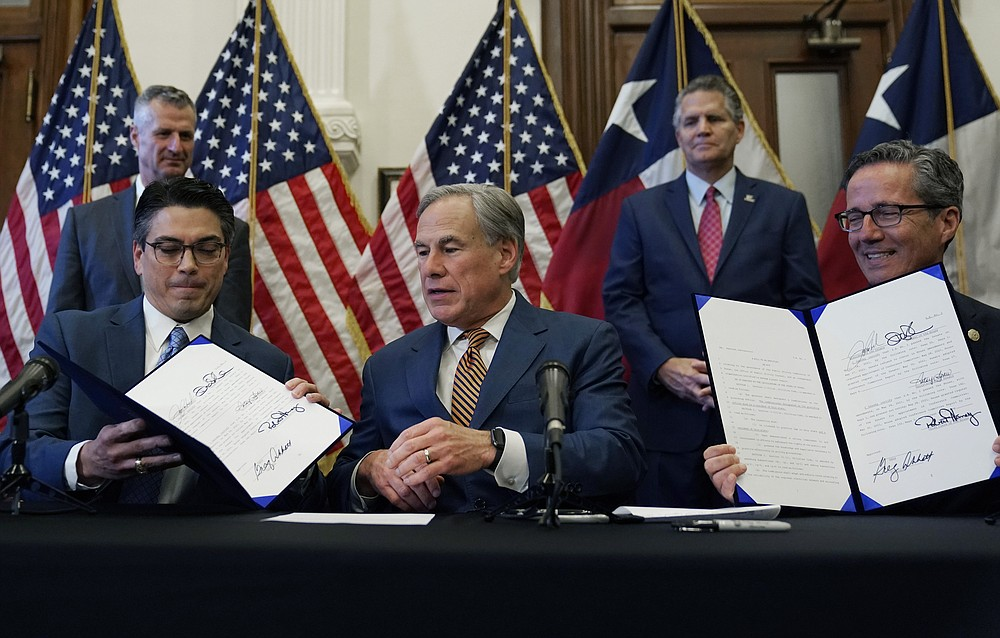 With help from State Representative Chris Paddie, left, and State Senator Kelly Hancock, right, Texas Gov. Greg Abbott, center, posts two energy-related bills he signed on Tuesday, June 8, 2021, in Austin, Texas.  Abbot enacted legislation to reform the Electric Reliability Council of Texas (ERCOT) and alter and improve the reliability of the state's electricity grid.  (AP Photo / Eric Gay)