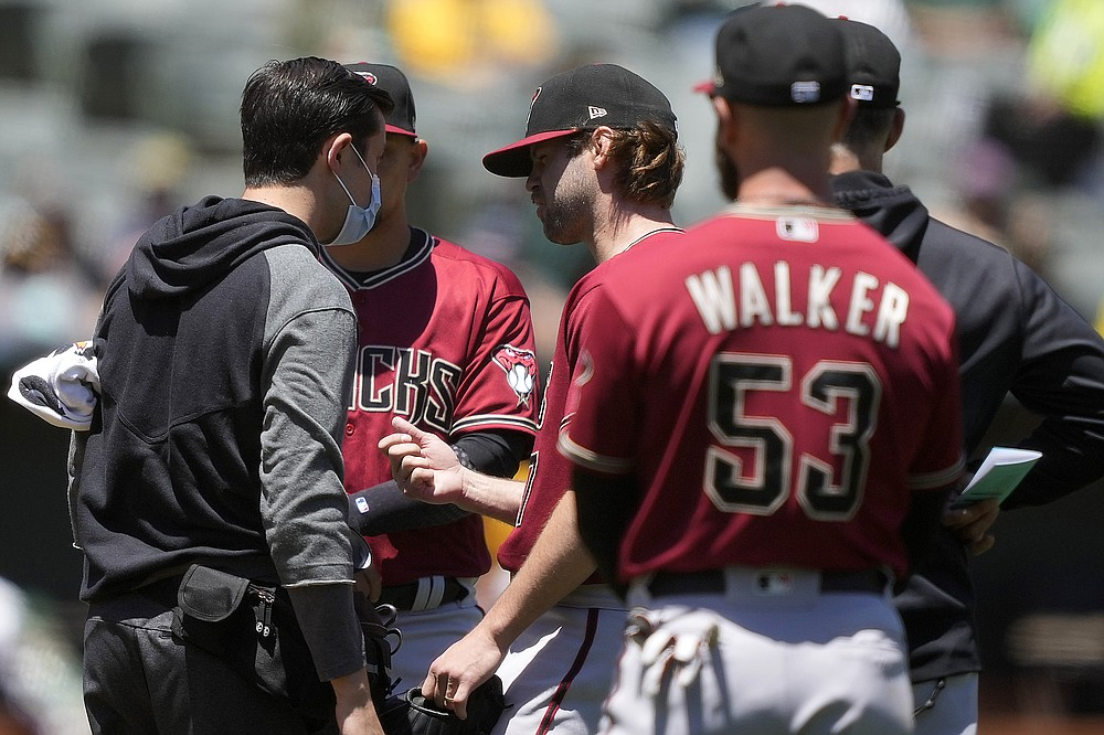 Arizona Diamondbacks pitcher Matt Peacock, center, has his throwing hand checked by the teams trainer during the second inning against the Oakland Athletics in a baseball game Wednesday, June 9, 2021, in Oakland, Calif. Matt Peacock left the game. (AP Photo/Tony Avelar)