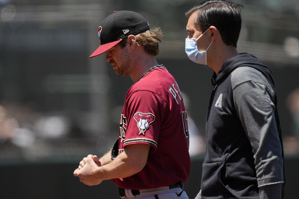 Arizona Diamondbacks pitcher Matt Peacock, left, leaves the game against the Oakland Athletics with an injury to his throwing hand during the second inning of a baseball game Wednesday, June 9, 2021, in Oakland, Calif. (AP Photo/Tony Avelar)