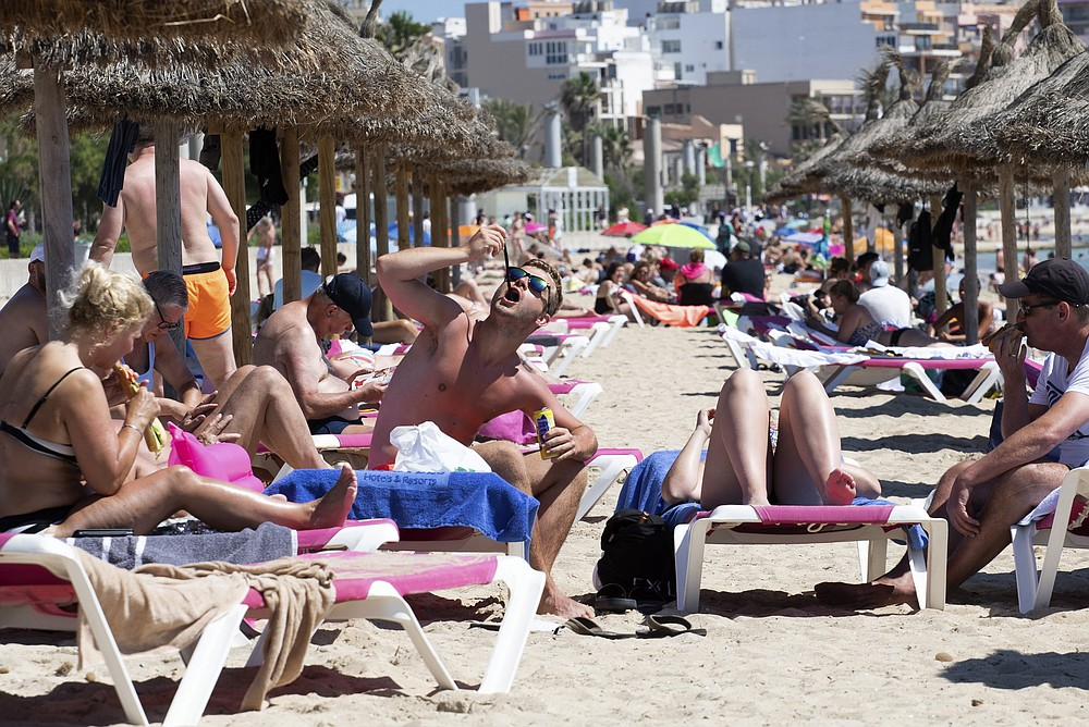Tourists sunbathe on the beach at the Spanish Balearic Island of Mallorca, Spain, Monday, June 7, 2021. Spain is jumpstarting its summer tourism season by welcoming vaccinated visitors from most countries as well as European visitors who can prove they are not infected with coronavirus. It also reopened its ports to cruise ship stops on Monday. (AP Photo/Francisco Ubilla)