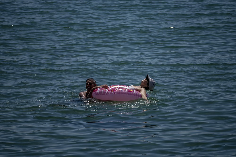 A couple cool off in the sea off the beach in Barcelona, Spain, Tuesday, June 8, 2021. Spain is jumpstarting its summer tourism season by welcoming vaccinated visitors from most countries as well as European visitors who can prove they are not infected with coronavirus. (AP Photo/Emilio Morenatti)