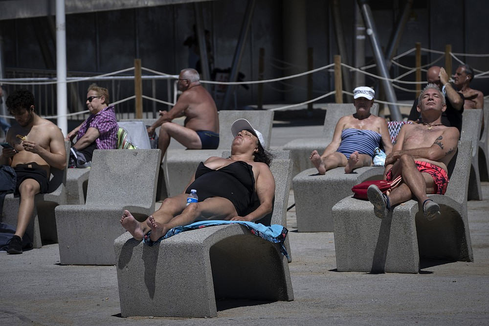 People sunbathe near the beach in Barcelona, Spain, Tuesday, June 8, 2021. Spain is jumpstarting its summer tourism season by welcoming vaccinated visitors from most countries as well as European visitors who can prove they are not infected with coronavirus. (AP Photo/Emilio Morenatti)
