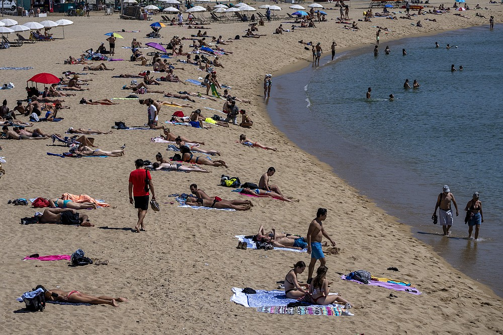 People sunbathe on the beach in Barcelona, Spain, Tuesday, June 8, 2021. Spain is jumpstarting its summer tourism season by welcoming vaccinated visitors from most countries as well as European visitors who can prove they are not infected with coronavirus. (AP Photo/Emilio Morenatti)