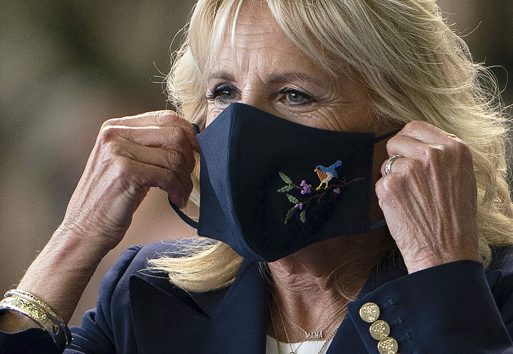 First lady Jill Biden adjusts her face mask after addressing U.S. Air Force personnel at RAF Mildenhall in Suffolk, England, ahead of the G7 summit in Cornwall, Wednesday, June 9, 2021. (Joe Giddens/Pool via AP)