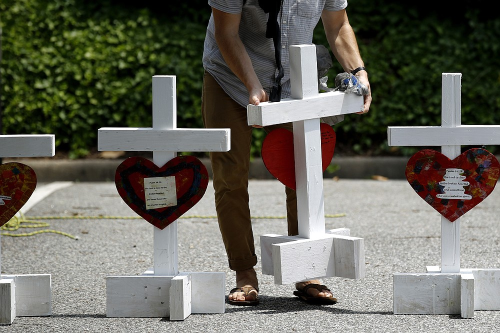 """FILE - In this June 2, 2019, file photo, a volunteer prepares to place crosses for victims of a mass shooting at a municipal building in Virginia Beach, Va., at a nearby makeshift memorial. DeWayne Craddock, a city engineer who fatally shot 12 people in a Virginia Beach municipal building in 2019 """"was motivated by perceived workplace grievances"""" that """"he fixated on for years,"""" according to findings released by the FBI on Wednesday, June 9, 2021.    (AP Photo/Patrick Semansky, File)"""