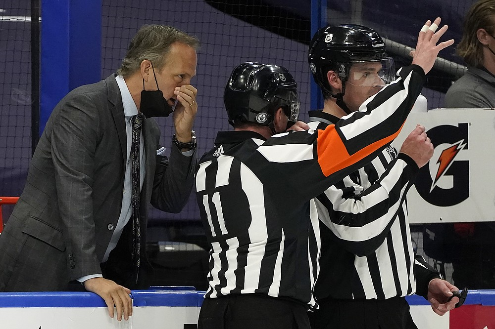 Tampa Bay Lightning head coach Jon Cooper talks to referee Kelly Sutherland (11) during the second period in Game 4 of an NHL hockey Stanley Cup first-round playoff series against the Florida Panthers Saturday, May 22, 2021, in Tampa, Fla. (AP Photo/Chris O'Meara)
