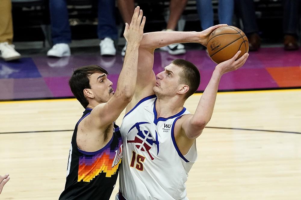 Denver Nuggets center Nikola Jokic (15) shoots as Phoenix Suns forward Dario Saric defends during the first half of Game 2 of an NBA basketball second-round playoff series, Wednesday, June 9, 2021, in Phoenix. (AP Photo/Matt York)